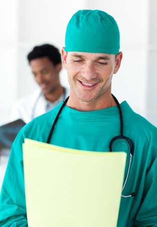 Attractive surgeon looking at a patients folder photo