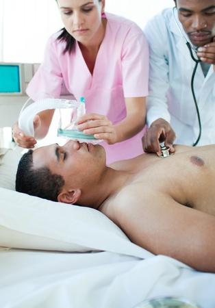 Nurse putting oxygen mask on a patient Stock Photo - 10112280