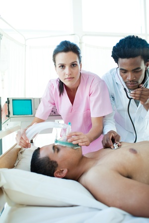 intensive care unit: A doctor and a nurse resuscitating a male patient