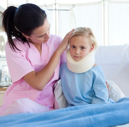A nurse looking after an upset girl with a neck brace photo