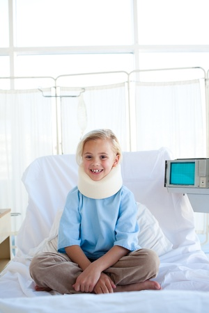 Smiling girl sitting on a hospital bed  photo