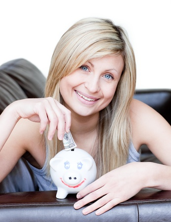 delighted: Delighted woman using a piggybank  Stock Photo