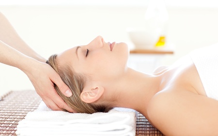 resting: Close-up of a beautiful woman receiving a head massage Stock Photo