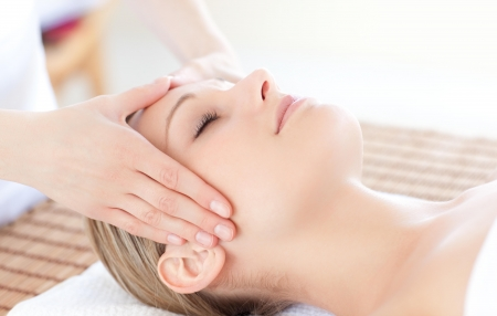 head down: Close-up of a bright woman receiving a head massage Stock Photo