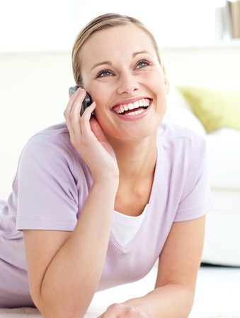 delighted: Delighted woman talking on phone lying on the floor  Stock Photo