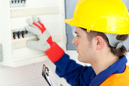 Caucasian electrician repairing a power plan photo
