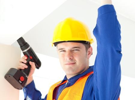 Joyful electrician repairing a power plan photo