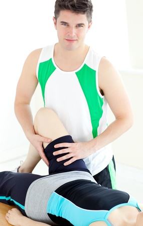 Attractive male physical therapist checking a womans leg  photo