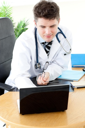 assertive: Assertive male doctor using a laptop sitting at his desk