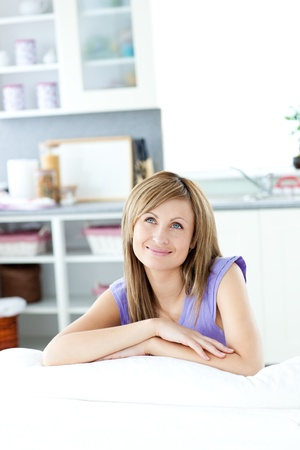 mirthful: Delighted woman thinking in the kitchen
