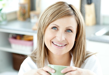 gratified: Happy woman holding a cup of coffee in the kitchen