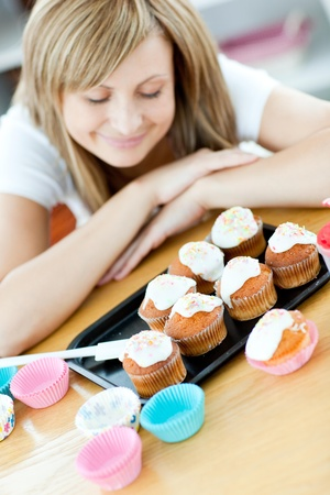mirthful: Caucasian woman preparing cakes in the kitchen