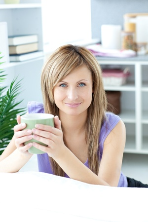 gratified: Young woman holding a cup of coffee in the kitchen