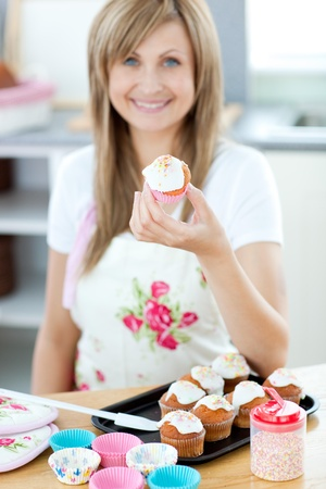 gratified: Young woman holding a cake in the kitchen  Stock Photo