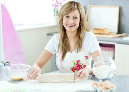 delighted: Delighted woman is preparing a cake in the kitchen
