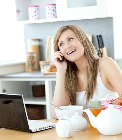 delighted: Delighted woman using a phone and laptop in the kitchen