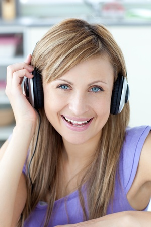 mirthful: Delighted woman using headphone in the kitchen