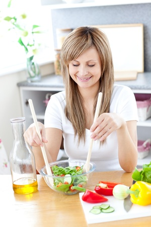 mirthful: Radiant woman preparing a salad in the kitchen