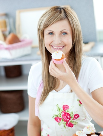 gratified: Delighted woman eating a little cake in the kitchen