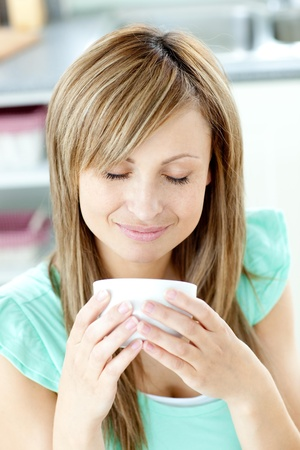 gratified: Delighted woman holding a cup of coffee in the kitchen