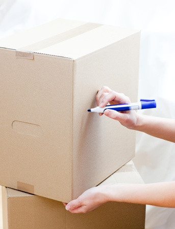 mortage: Cute woman writing on a box at home