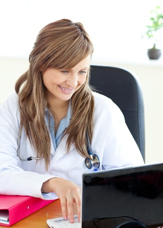 Smiling female doctor working with a laptop  photo