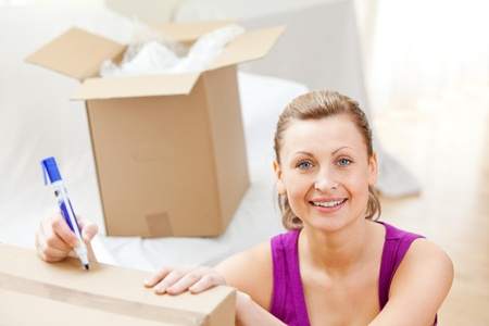 gratified: Cute woman writing on boxes using a pen  Stock Photo