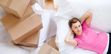 gratified: Cheerful woman relaxing between boxes  Stock Photo