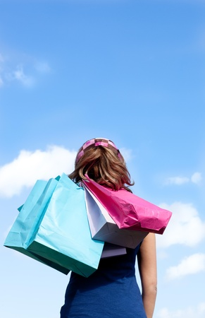 Smiling woman holding shopping bags outdoor  photo