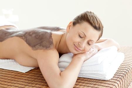 mud woman: Radiant woman enjoying a mud skin treatment  Stock Photo