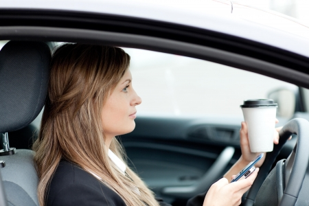 Blond businesswoman sending a text while driving photo