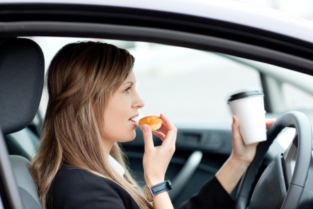 drink and drive: Charming businesswoman eating and holding a drinking cup while driving