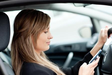 conduciendo: Bella empresaria enviar un texto mientras se conduce