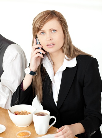 Worried businesswoman talking on phone while having breakfast Stock Photo - 10111771