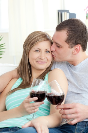 Portrait of an affectionate young couple drinking red wine photo