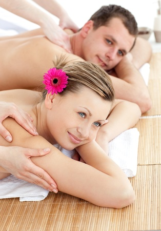 Smiling young couple receiving a back massage photo