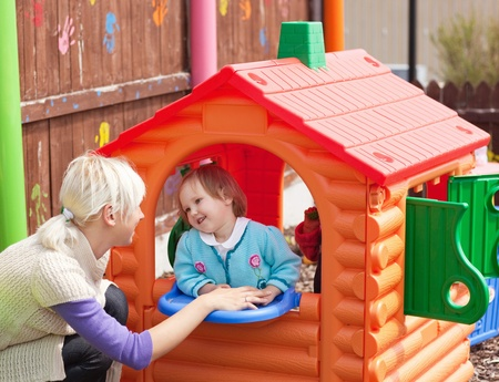 Sweet girl standing in a small house at the playground photo