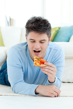 A young man eating pizza photo