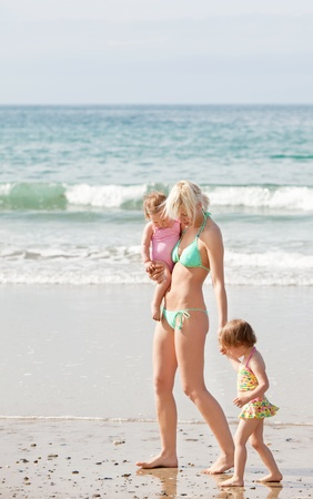 A young mother walking at the beach with her children photo