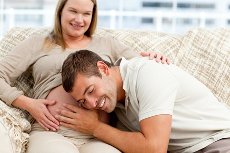 Attentive future dad listening to the belly of his wife sitting on the sofa Stock Photo - 10161987