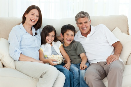 they are watching: Family watching tv while they are eating popcorn Stock Photo