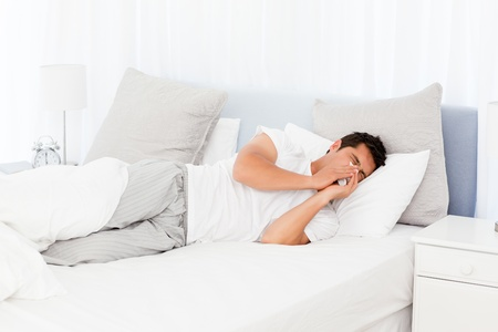 inconvenience: Sick man blowing his nose lying on his bed