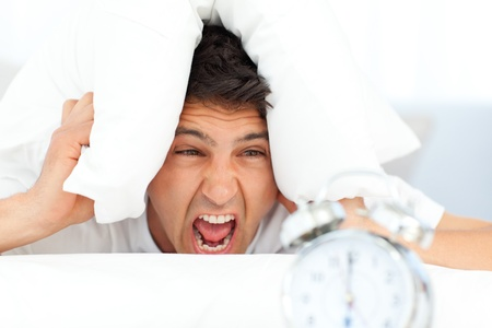 morning routine: Angry man putting his head under the pillow Stock Photo