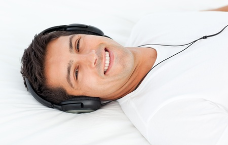 Handsome man listening to the music lying on his bed Stock Photo - 10212790