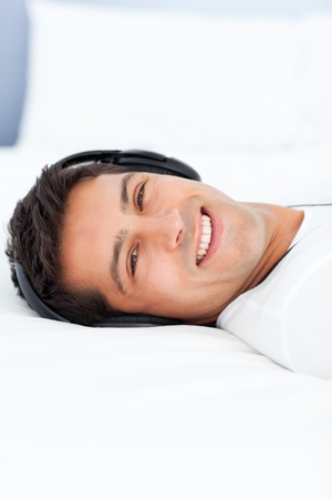 Cheerful man listening music with headphones lying on his bed photo