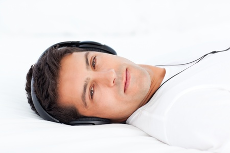 casua: Charismatic man listening music lying on his bed