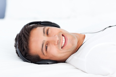 Portrait of a happy man listening music lying on his bed Stock Photo - 10213592