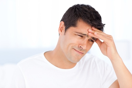 Worried man having a headache sitting in his bedroom Stock Photo - 10207566