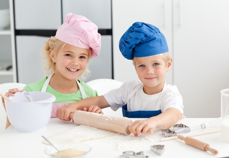 preparation: Happy brother and sister preparing a dough standing in the kitchen
