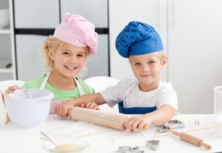 niños cocinando: Hermanos preparando un permanente de masa en la cocina y feliz